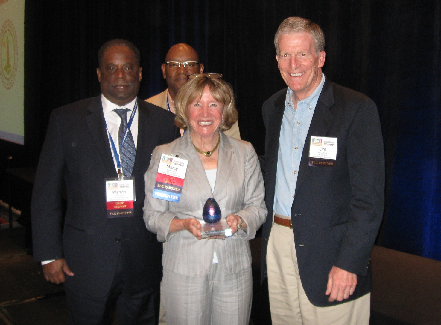Warren Harris, Marcy Sims and City Manager Jim Spore accept award from Bill Horne