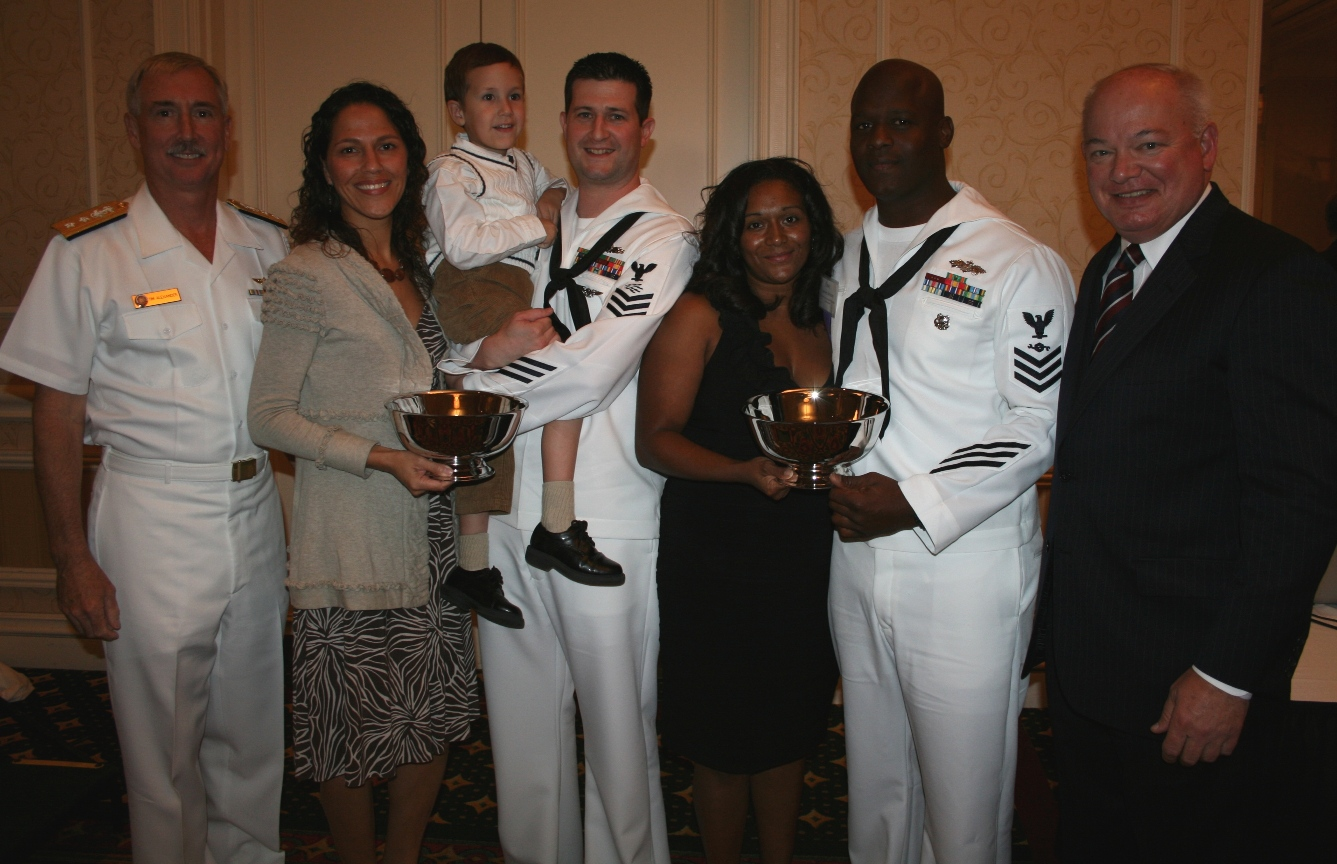 (from left) RADM Tim Alexander; Kristina Halleran; IT1 James Halleran holding son Anthony; Elizabeth Simons; CM1 James Simons; and Norfolk Mayor Paul Fraim