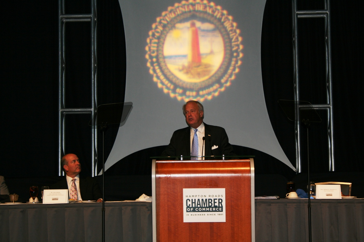Virginia Beach Mayor Will Sessoms addresses crowd while John Wilson, Chair, Virginia Beach Division of the Hampton Roads Chamber of Commerce looks on